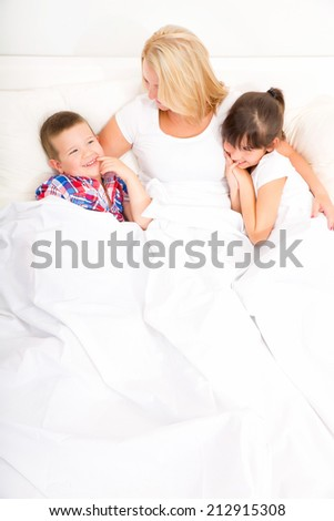 A mother relaxing in bed with her daughter and her son.