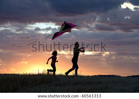 A mother runs to fly a kite with her daughter behind her. - stock photo