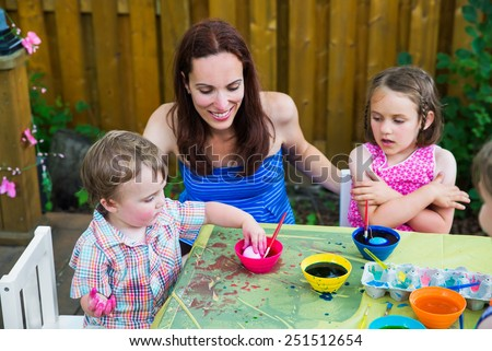 A Mother smiling at her boy decorating eggs as he puts his Easter egg in pink color dye while outside  During the spring season in garden setting.  Sister watches.  Part of a series.    - stock photo