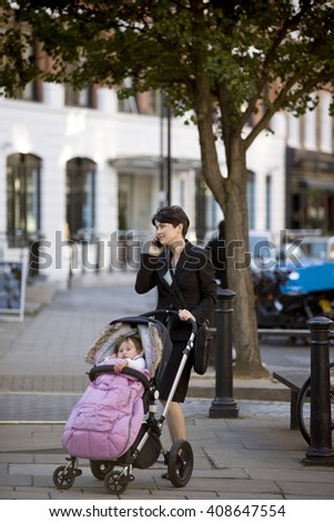 A mother standing with a stroller in the street, talking on her mobile phone - stock photo