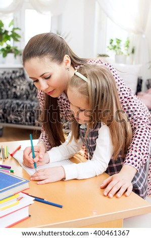 A mother teaches her young daughter  to hold the pencil
