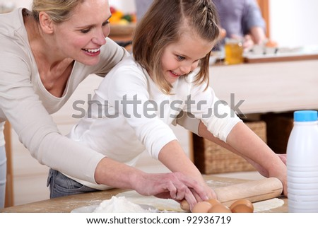 A mother teaching her daughter how to bake. - stock photo