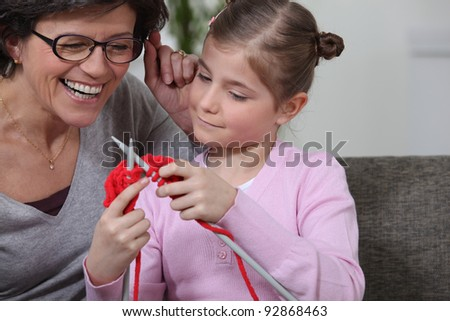 A mother teaching her daughter how to knit. - stock photo