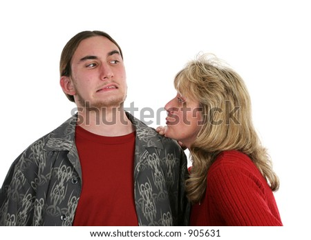 A mother trying to give her teen son a kiss.