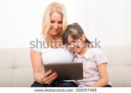 A mother using with her daughter a Tablet PC. - stock photo