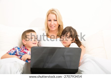 A mother using with her son and daughter a laptop computer in bed.  - stock photo