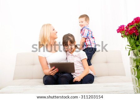 A mother using with her son and daughter a Tablet PC. - stock photo