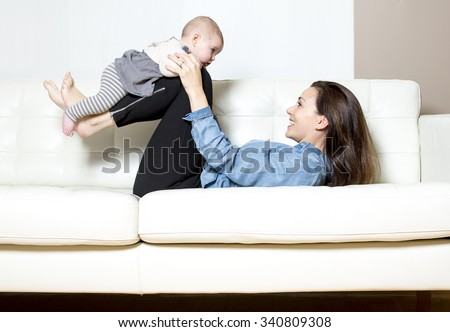 A Mother with baby on the sofa taking good time - stock photo