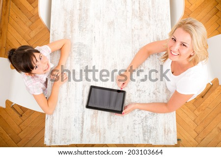A mother with her daughter using a tablet PC at home. - stock photo