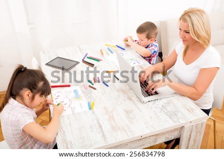 A mother with her kids with at a laptop at home.