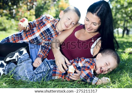 A mother with is two son with a apple background