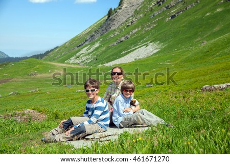A mother with kids in the summer in the mountains