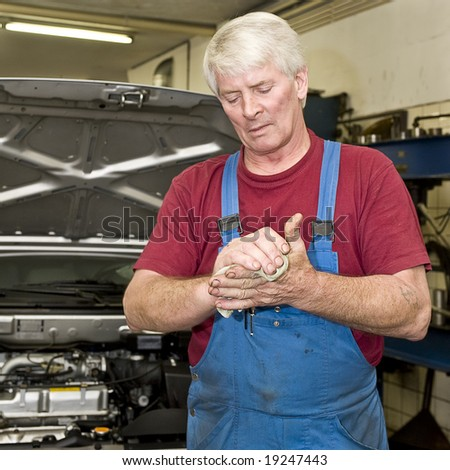 A motor mechanic cleaning his greasy hands after servicing a car. Focus on his hands - stock photo