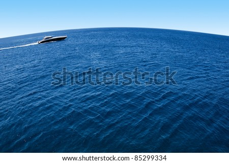 A motor yacht drives through blue planet - stock photo