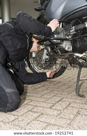A motorcyclist inspecting his motorbike at a gas station - stock photo