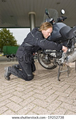 A motorcyclist inspecting his motorbike at a gas station, looking worried