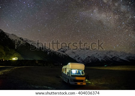 A Motorhomes Parked Under Milky Way Galaxy Rising Above Snow Capped Southern Alps Mountain Range At Mount Cook National Park, Canterbury, New Zealand.  Image Noise Due To High ISO  - stock photo