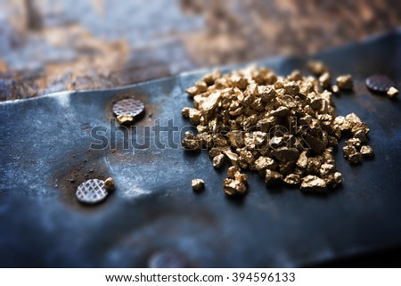a mound of gold on a old wooden chest. Shallow depth of field.