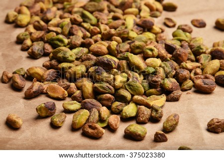 A mound of shelled pistachios on brown kraft paper - stock photo