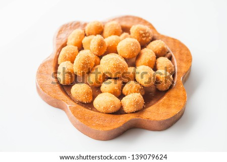 A mound of spicy peanut snack in wood dish - stock photo