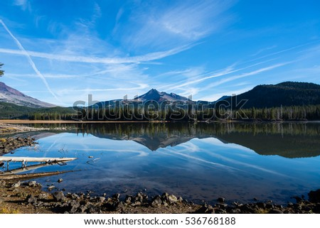 A mountain and a lake landscape with reflections of sky with clouds