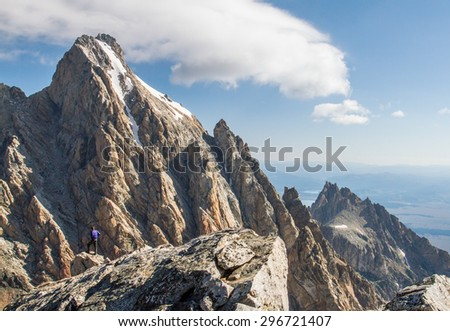 a mountain climber stands atop one peak while investigating a taller mountain before him
