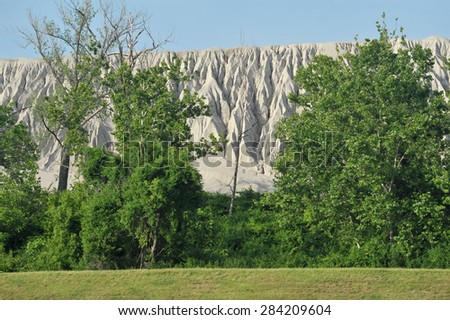 A mountain of gravel from a quarry rises upon the treetops - stock photo
