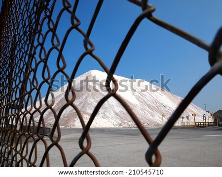 A mountain of road salt sits locked securely behind a chain link fence. - stock photo