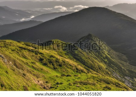 A mountain range and strong hills, covered with green lush grass, shrubs. The outgoing sun, small clouds and the beautiful color of the sky. Carpathian mountains, Ukraine
