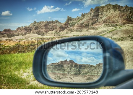 A mountain range of the colored hills as viewed through the rear-view mirror window of a car by the roadside in Badlands National Park in South Dakota.