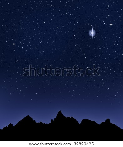 A mountain range silhouetted by a star-filled night sky. - stock photo