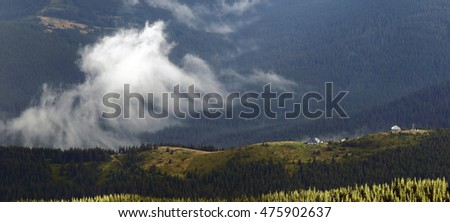 A mountain range with clouds and houses