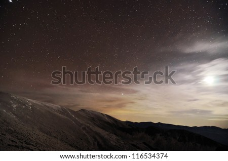 A mountains landscape at night with moonlight and stars - stock photo
