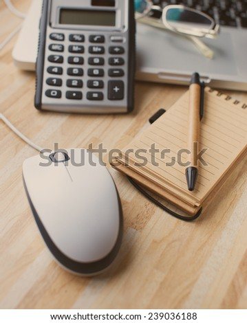 A mouse next to a calculator and a paper diary