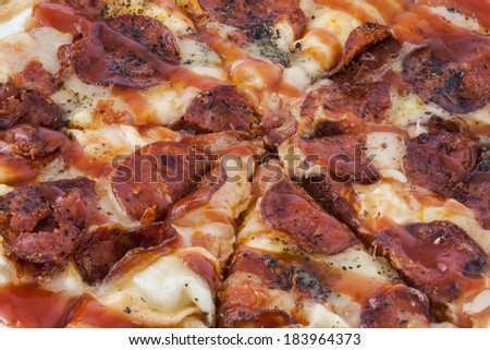 A mouthwatering closeup of a pepperoni pizza pie cut into slice