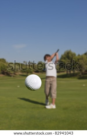 "A ""moving"" golf ball in the foreground and a player in the background, out of focus."