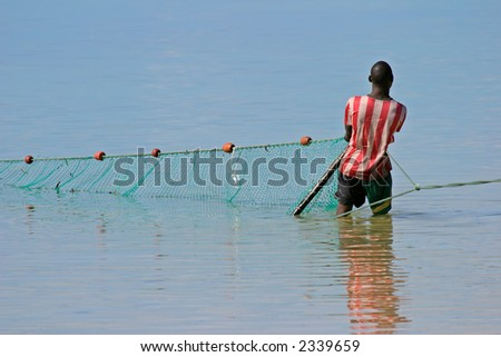A mozambican fisherman pulling a fishing net from the water - stock photo