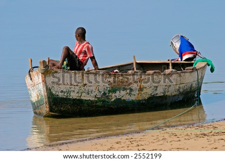 A mozambican fisherman sitting on a fishing boat - stock photo