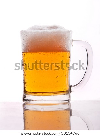 A mug of beer with froth and slight spill
