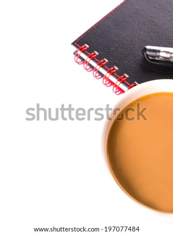 A mug of coffee with creamer with black notebook and a pen over white background