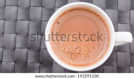 A mug of hot chocolate beverage on a woven table mat. - stock photo