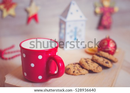 A mug of milk with cookies and christmas decorations