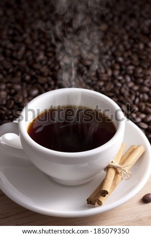 A mug of steaming coffee on a saucer. - stock photo