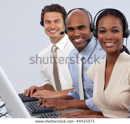 A multi-ethnic business people with headset on in a line smiling at the camera