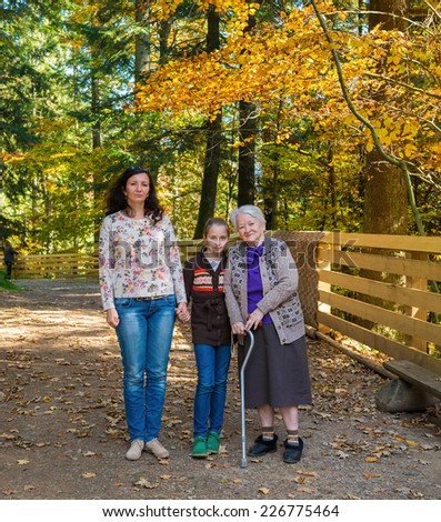 A multi generation portrait of a happy grandmother with her daughter and granddaughter outdoor - stock photo