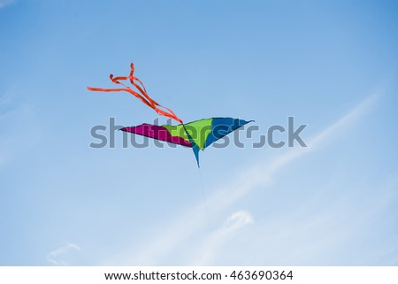 A multicolored kite flying against a blue sky.