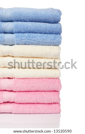 A multicolored towels stacked and isolated on white background. Shallow depth of file - stock photo