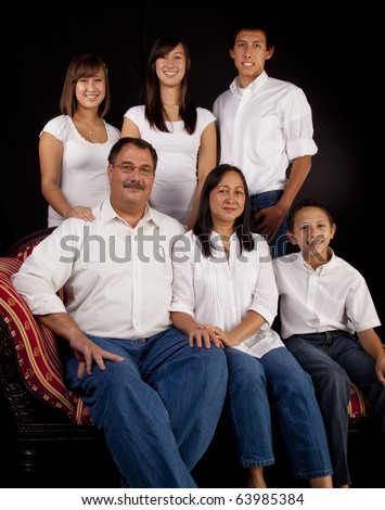 A multicultural American family of six in a seated  formal studio portrait with a black  background. - stock photo