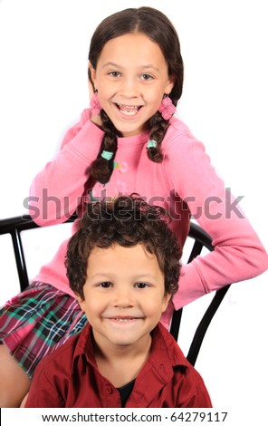 A multiracial girl standing behind  a toddler  boy sitting on a stool with a white  background - stock photo