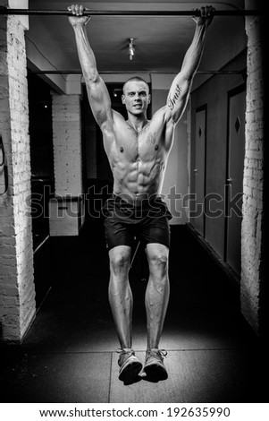 A muscled man doing pullups in a gym - stock photo